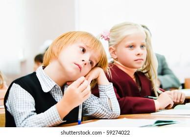Small children sit in desks