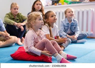 Small children sitting on the floor listening attentively to the teacher in kindergarten in preschool