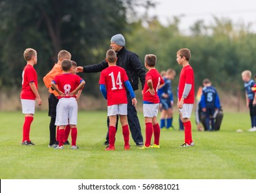 Small children soccer players playing football and coaches training them