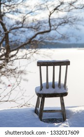 A small children wooden chair left outside in the snow.