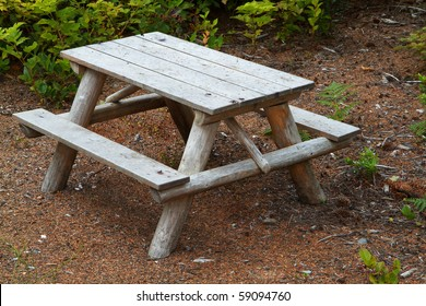 Small children's wood picnic table with green foliage in background