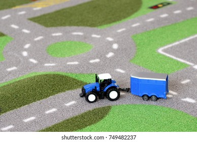 A small child's toy tractor and trailer on a road mat carpet