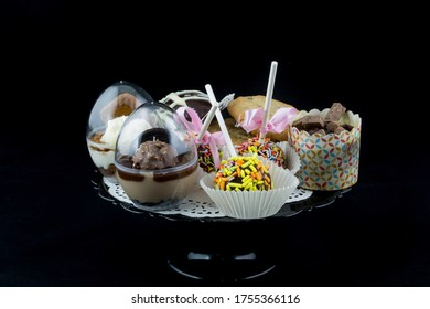 small chocolate cakes and cookies on a plat, black background