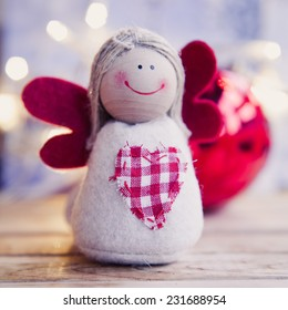 Small christmas angel with red wings. Family and child, christmas gifts.Christmas decoration. Colorful window in the city during winter.