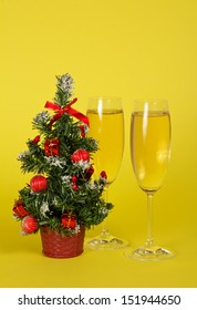 Small Christmas fir-tree in a pot, and two wine glasses with champagne on a yellow background