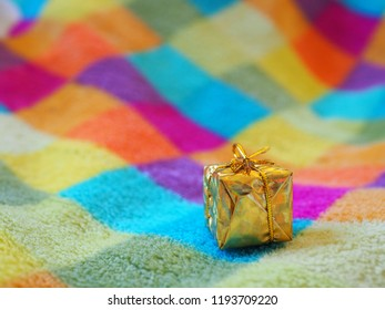 A small christmas gift on a colored checkered blanket
