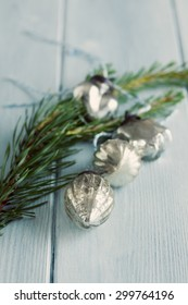 Small christmas glass decorations with blue and white string, laying on a blue wooden floor with a small pine branch next to them. Focus is on the front bauble with the others out of focus.