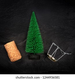 A small Christmas tree with a champagne cork and closure, shot from above on a black background with copy space, a neat New Year greeting card design