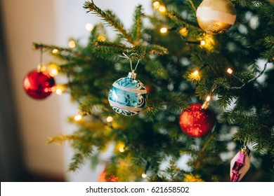 A small Christmas tree in a pot, decorated with balls, garlands and lights.