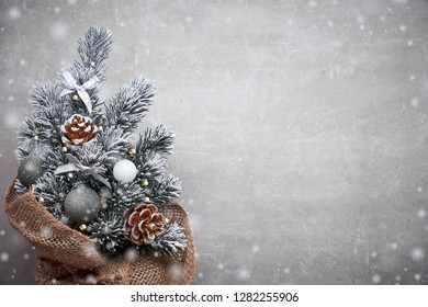Small Christmas tree in sackcloth decorated with red baubles and berries on light stone background with copy-space