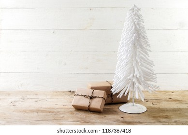 small christmas tree from white flocked wire and gifts in kraft paper on a rustic wooden table, white painted vintage background with large copy space, selected focus