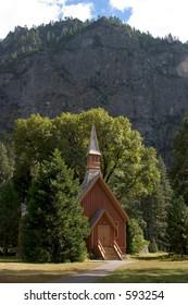 Small church at the base of a sheer wall of granite, in Yosemite Valley.