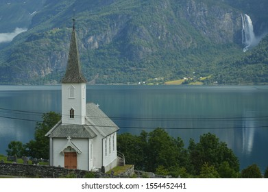 A small Church with a cemetery  surrounded by tall mountains and water falls in Luster municipality, Norway