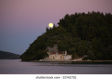 Small church in the foreground and rising moon in the back of the island. Early evening giving purple tone for the sky. Lefkas, Greece.