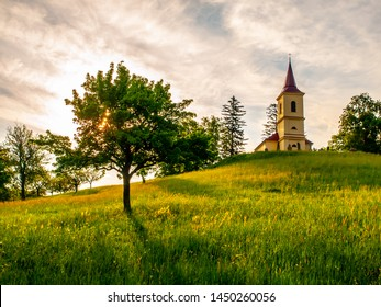 Small church in the middle of lush green spring landscape on sunny day. St. Peter and Pauls church at Bysicky near Lazne Belohrad, Czech Republic. - Shutterstock ID 1450260056
