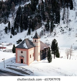 A small church in a snowy landscape with surrounding trees