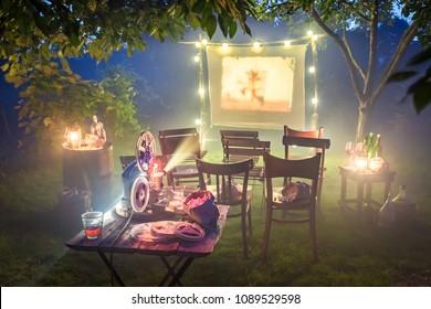 Small cinema with retro projector in summer garden