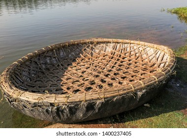 A small circular lightweight boat or coracle constructed of natural materials woven together in an intricate pattern to give strength and buoyancy. The craft is resting on a grass bank beside a river.