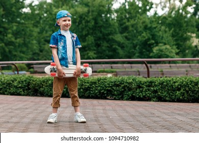A small city boy and a skateboard. A young guy is standing in the park and holding a skateboard. City Style. City children. A child learns to ride a skateboard