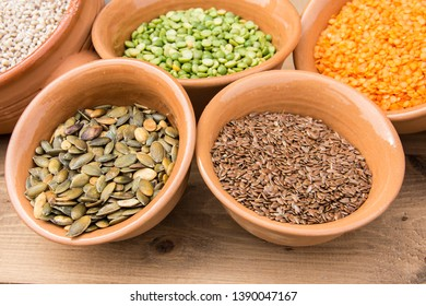 Small clay bowls with various seeds: pumpkin seeds, flaxseed, red lentils, green peas, barley grains.