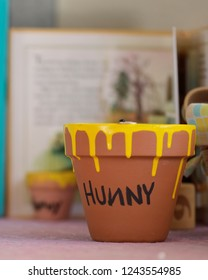 "A small clay pot dripped with yellow paint and ""hunny"" written, with a children's book blurred behind."