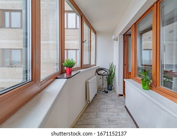 Small clean cozy balcony with windows in tiny city apartment with plants