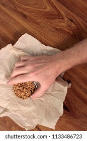 Small clear plastic container of sweet and crunchy granola food snack being held by a caucasian hand. Male hand holding sweet granola snack food in a clear plastic container over a napkin on a table.