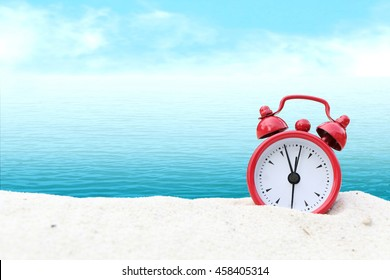 small clock on white sea sand and blur ocean background