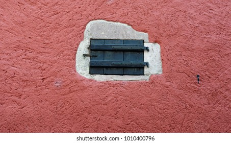 Small closed door in red plaster wall