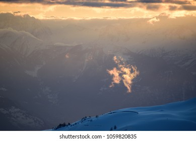 small cloud illuminated by warm light in the swiss alps
