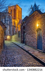Small cobbled street in York at night with the famous Minster in the back