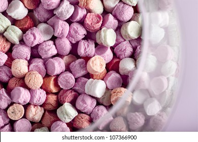 small colored candies in a glass jar