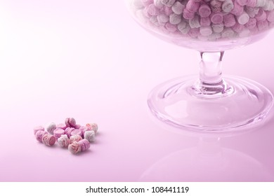 small colored candies in a glass jar and some out