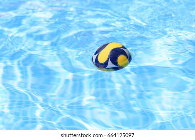 A small colored foam balloon floating on the pool surface