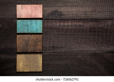 Small colored pieces of wood on a dark wooden table, with space for your text
