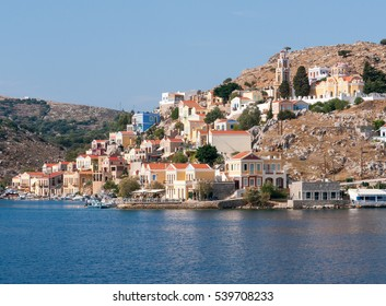 small colored stone house located on the slopes of the mountains in the bay on the coast of the Aegean Sea, Ano Symi city, Simi - one of Dodecanese island, Greece