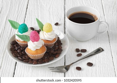 Small colorful cakes in plate and cup of coffee on white wooden table