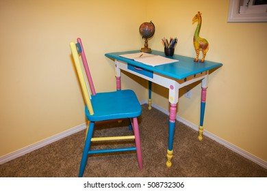 A small colorful children's desk and chair with notebook and globe and pencil crayons on it