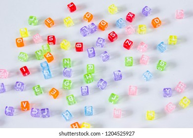 Small colorful cubes with English alphabet letters spilled at white table