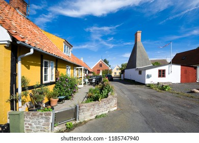 Small colorful half-timbered houses in Aarsdale, Bornholm, Denmark. Chimney of traditional smokehouse in the background