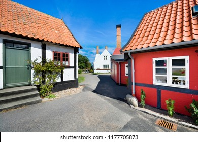 Small colorful half-timbered houses in Gudhjem, Bornholm, Denmark. Chimneys of traditional smokehouses in the background.