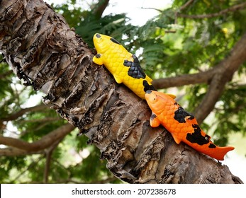 small colorful hand painted garden decoration sculpture installed on coconut tree outdoor in form of carp, KOI fish in yellow orange and black swimming climbing on the tree