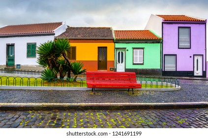 Small colorful houses street scene. Small colorful city houses. Red bench at small colorful houses. Red bench at small colorful town houses