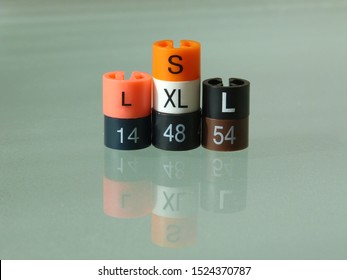 Small colorful plastic markers, size indicators from cloth hangers depicting dress sizes. S for small, L for large, XL for extra large. low angle abstract view. clothing sizes symbol. copy space.
