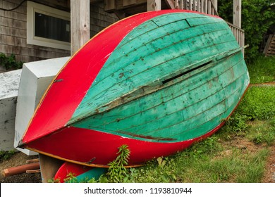A small colorful rowboat skiff sits on it's side at seasons end on a New England Dock