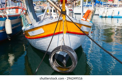 Small colorful wooden fishing boat moored in Propriano town, Corsica, France