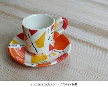 Small colourful coffee cup on a saucer on a table