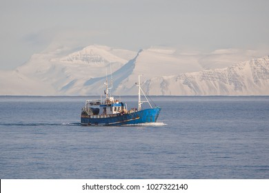 Small commercial fishing boat with snowy mountains in background.