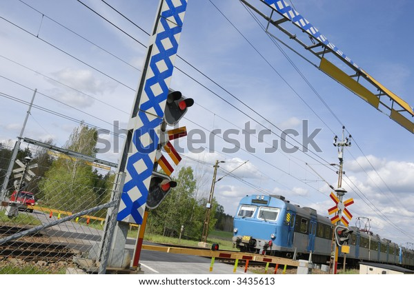 small commuter-train passing a country crossing