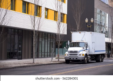 Small compact semi truck with a box trailer body for transportation furniture and home goods and other commercial cargo is on the road of a city street near the modern office building